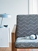 Armchair with black and white upholstery and table lamp on white side table