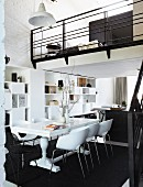 Compact living - white wooden table and modern shell chairs on black carpet in open-plan interior with mezzanine