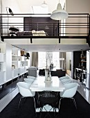 White dining set with modern shell chairs on black rug in narrow apartment with bedroom in mezzanine