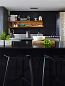 Black, designer bar stools at black counter; wooden shelves on dark wall in background