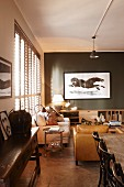Artistic picture of horse on dark grey wall in lounge area with wooden and upholstered furniture and vintage atmosphere