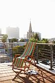 Vintage-Liegestuhl mit Streifenmuster auf Holzterrasse und modernem Büstungsgeländer; Blick auf Kapstadt