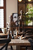 Two carved figurines of bald men and other hand-crafted wooden objets d'art on rustic wooden table in vintage interior