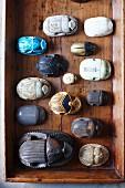 Various artistic carvings of scarab beetles arranged in vintage wooden crate
