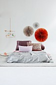 Shimmering combination of textiles on futon in front of decorative paper fans on wall