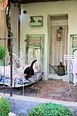 Katze auf Vintage Metallbett auf Veranda eines Bauernhauses