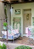 Vintage Metallbett auf Veranda eines Bauernhauses