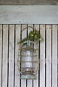 Old lantern with dried posy of garden flowers hanging on wooden lath wall