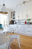 White fitted kitchen with panelled doors, dining area with vintage chairs and retro lamp in foreground