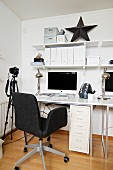 White home office with dark grey swivel chair, camera on tripod and black star ornament