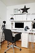 Weisses Home Office mit dunkelgrauem Drehstuhl, Kamera auf Stativ und schwarzem Deko Stern