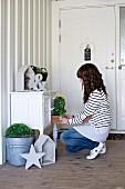 Frau bei der Dekoration einer antiken Dielenkommode mit Pflanztöpfen und Vintage Objekten