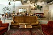 Samtbezogene Couch und Sessel in großem Loft; im Hintergrund Esstische auf einem Podest und ein goldgerahmter Spiegel an gekachtelter Wand