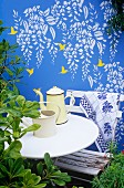 Wall deco with humming birds and wisteria on blue-painted garden wall behind white table, chair and coffee pot