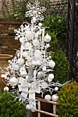 Imitation Christmas tree with white baubles and decorations in wintery garden