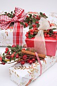 Wrapped Christmas gifts decorated with ribbons, rosehips and cinnamon sticks