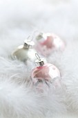 Christmas tree baubles amongst feathers