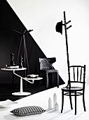 Chair artistically modified into coat stand and white side table against wall with black and white 3D effect