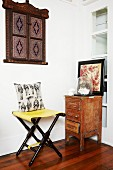 Folding stool in corner next to small, vintage cabinet & wooden objet d'art on wall