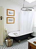 Vintage bathtub with shower curtain in country-style, wood-clad bathroom with tiled floor