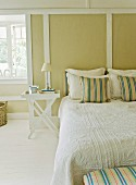 Double bed with scatter cushions and white bedspread in front of pale green wood-panelled wall in rustic atmosphere
