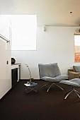 Armchair and matching footstool on dark carpet in minimalist interior