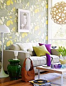 Sofa and standard lamp against wall with floral wallpaper