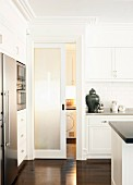 Contemporary fitted kitchen with white, coffered doors and dark parquet floor