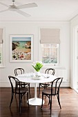 Dining area with classic Thonet chairs and white tulip table on dark wooden floor; framed picture flanked by windows with Roman blinds