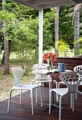 White, designer outdoor furniture on wooden terrace of weekend house in forest