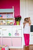 Girl next to white sideboard with storage boxes in compartments and dolls' house on surface against hot pink wall