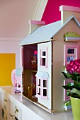 Dolls' house on white surface in child's bedroom