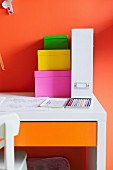 Stack of colourful, cardboard storage boxes and white box file on desk against orange wall