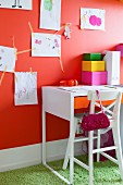 Tall, white chair at desk below child's drawings on orange wall