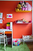 Colourful shelves of soft toys and books on orange wall and desk to one side in child's bedroom