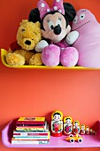 Soft toys and books on colourful shelves on orange wall
