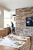 Set dining table in front of TV on old brick wall with view of open-plan kitchen in background
