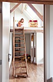 Girl playing on mezzanine level above bedroom accessed via samba stairs