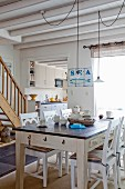 Rustic dining table and white wooden chairs in open-plan interior with maritime character