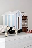 Maritime Dekoration - Miniatur Strandhäuschen weiss-blau gestreift und kleine Figuren auf weißem Schrank