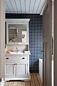 Blick durch offene Tür auf weissen Holzschrank mit Spiegelaufsatz und eingebautem Waschbecken vor dunkler Mosaikfliesenwand