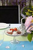 Gedeckter Tisch mit Dessert und Blume im Garten
