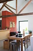 Retro Hocker und Stühle am Esstisch aus Holz, gegenüber Theke neben rotbrauner Wand, in rustikal modernem Wohnraum