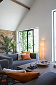 Lounge area with grey sofa, coffee table, terrace doors, house plants and standard lamp with paper lampshade