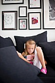 Little girl listening to music amongst black cushions in front of collection of black-framed pictures