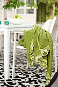 Light green blanket on white chair next to table on black and white patterned rug