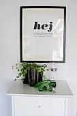 Pflanzengefässe, Schale und Windlicht aus Glas auf weisser Kommode, an Wand Begrüssungsbild