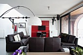 Black leather sofa set in lounge area and arc lamp with white paper lampshade in loft apartment