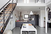 White dining table in front of open-plan kitchen with dark grey cabinets in modern loft apartment with retro ambiance; metal staircase leading to mezzanine