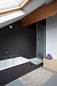 Designer, attic bathroom with fitted bathtub and shower cubicle against black-tiled wall